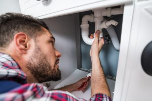 Male plumber in Upper Hutt fixing the sink