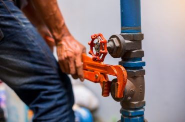 Plumber in Upper Hutt using a wrench to repair a water supply pipe